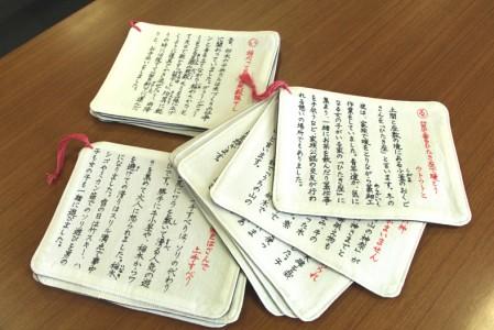 カルタの解説書布カードも。文字はすべて手書きです。