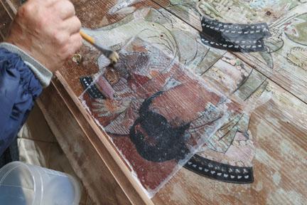 絵馬の絵具が剥落するのをとめるため、専門の和紙の上から剥落とめの溶液を塗ります。