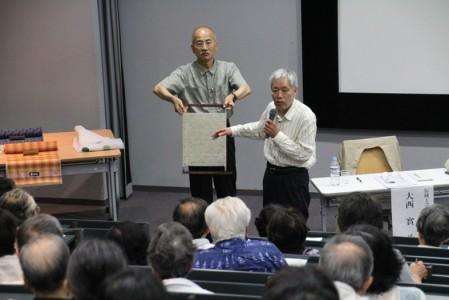 ハネと呼ばれる織物の模様をつくる染め台の解説をする大西さん、辻研究員