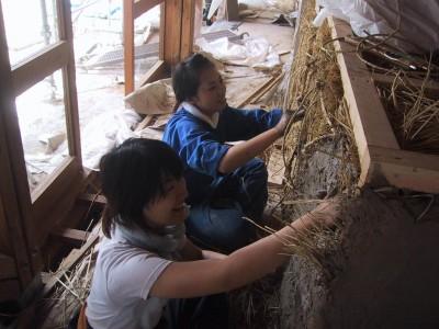 カウンター下のストロー・ベイル(藁をサイコロ状にした塊)の上から土を塗る