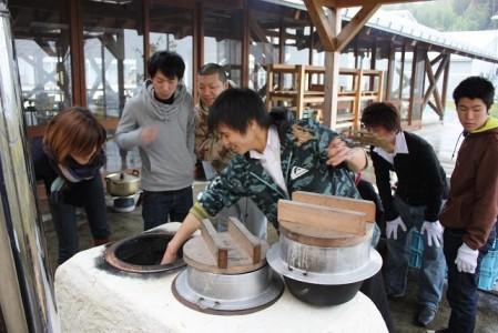 釜戸での炊飯指導を受ける学生たち