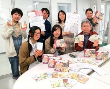 完成を喜び合う学生スタッフと永江研究員